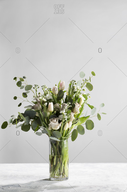 Floral arrangement in glass vase with roses and eucalyptus on a textured background with copy space