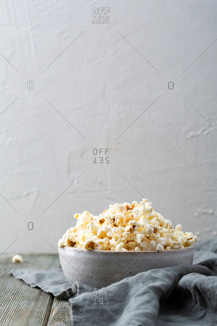 Close up of bowl with popcorn on gray wooden table