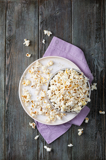 Overhead view of homemade popcorn in bowl on wooden table