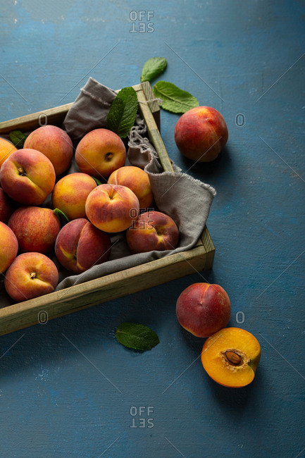 Full crate filled with summer peaches on blue background