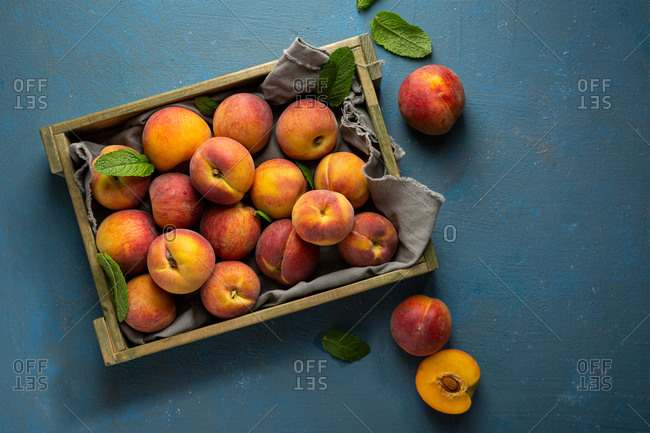 Overhead view of crate with summer peaches on blue background