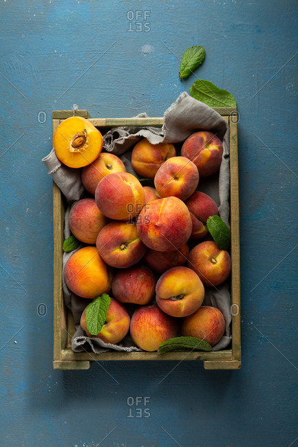 Top view of crate with summer peaches on dark blue surface