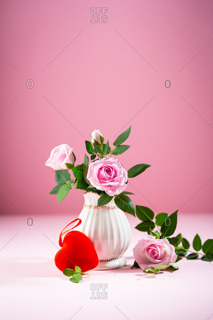 Pink roses in white vintage vase and red heart decor