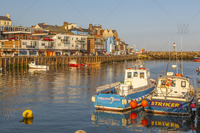 September 14, 2020: View of harbor boats and harborside shops in Bridlington Harbor at sunset, Bridlington, East Yorkshire, England, United Kingdom, Europe