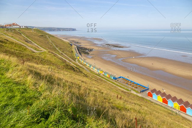 View of colorful beach huts on West Cliff Beach, Whitby, North Yorkshire, England, United Kingdom, Europe