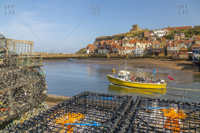 September 21, 2020: View of St. Mary's Church and restaurants, houses and boats on the River Esk, Whitby, Yorkshire, England, United Kingdom, Europe