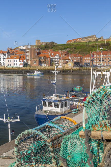 September 21, 2020: View of St. Mary's Church and fishing baskets, houses and boats on the River Esk, Whitby, Yorkshire, England, United Kingdom, Europe