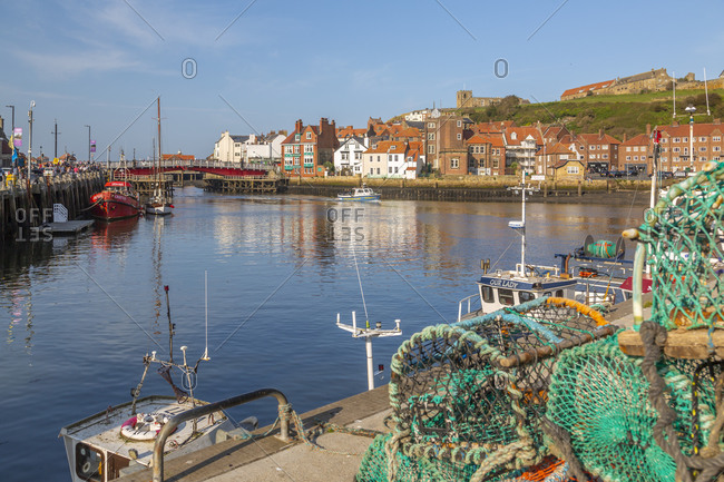 September 21, 2020: View of St. Mary's Church and fishing baskets, houses and boat on the River Esk, Whitby, Yorkshire, England, United Kingdom, Europe
