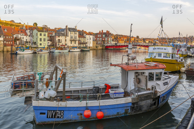 September 21, 2020: View of riverside houses and fishing boats on River Esk at sunset, Whitby, Yorkshire, England, United Kingdom, Europe