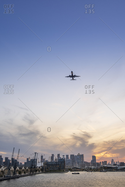 September 18, 2020: A plane arriving at the City of London airport with the Victoria Dock and skyline of the financial district, Docklands, London, England, United Kingdom, Europe