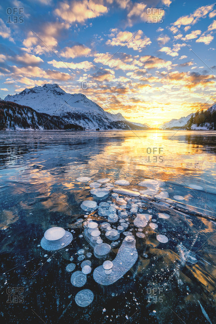 Clouds in the burning sky at sunset on Piz Da La Margna and ice bubbles trapped in Lake Sils, Engadine, Graubunden, Switzerland, Europe
