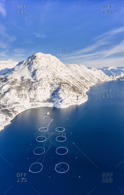 Aerial view of snow capped mountains and salmon fish farm in the Arctic sea, Oksfjord, Loppa, Troms og Finnmark, Norway, Scandinavia, Europe