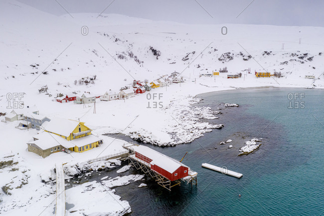 Fishing village of Sorvaer framed by the cold sea during a snowy winter, Soroya Island, Hasvik, Troms og Finnmark, Arctic, Norway, Scandinavia, Europe