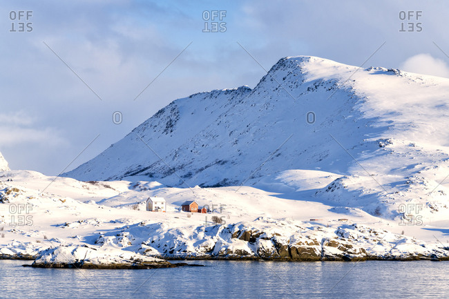 Winter sun over isolated fishermen huts in the snow, Hasvik, Soroya Island, Troms og Finnmark, Arctic, Northern Norway, Scandinavia, Europe