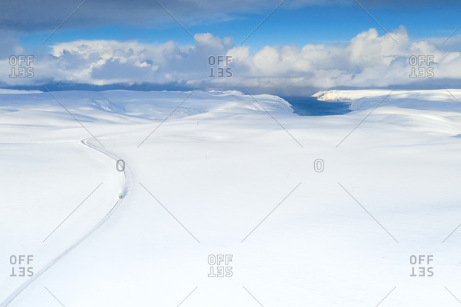 Aerial view of empty road towards Nordkapp (North Cape) crossing the landscape covered by deep snow, Troms og Finnmark, Norway, Scandinavia, Europe