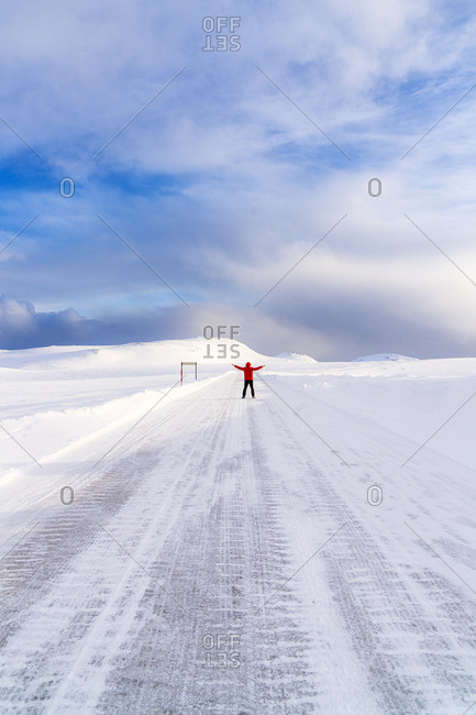 Happy man with arms raised standing on the snowy icy road towards Nordkapp (North Cape), Troms og Finnmark, Northern Norway, Scandinavia, Europe