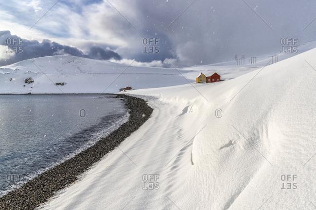 Snowfall on the lone wood houses facing the Arctic sea, Skarsvag, Nordkapp, Troms og Finnmark, Northern Norway, Scandinavia, Europe