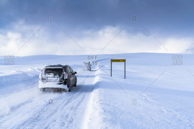 March 2, 2020: Off road vehicles driving on the icy road towards Nordkapp (North Cape) in the deep snow, Troms og Finnmark, Northern Norway, Scandinavia, Europe