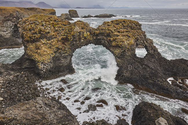 A rock arch among basalt lava cliffs at Arnastapi, on the coast of the Snaefellsnes peninsula, west Iceland, Polar Regions