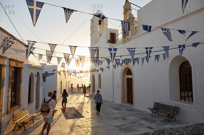 September 9, 2020: Sunset in Plaka, the main town on Milos island, with Greek Orthodox feast decoration on the church square with pebble mosaic, Plaka, Milos, Cyclades, Greek Islands, Greece, Europe