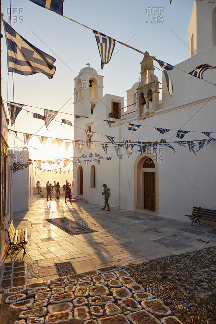 September 9, 2020: Sunset in Plaka, the main town on Milos, with Greek Orthodox feast decoration on the church square with pebble mosaic, Plaka, Milos, Cyclades, Greek Islands, Greece, Europe