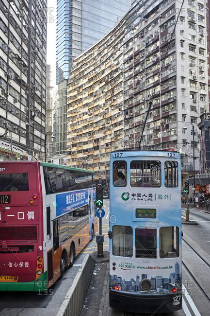 Hong Kong, China - September 23, 2016: A modern double decker tram beside a double decker bus on a street in the Central part of Hong Kong