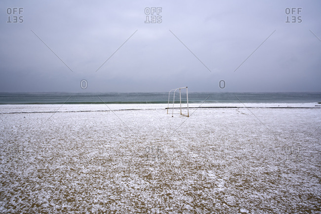 Snowfall on an empty winter beach with visible sea evaporations after a snow storm on the coast of Kamchiya reserve near Varna, Bulgaria