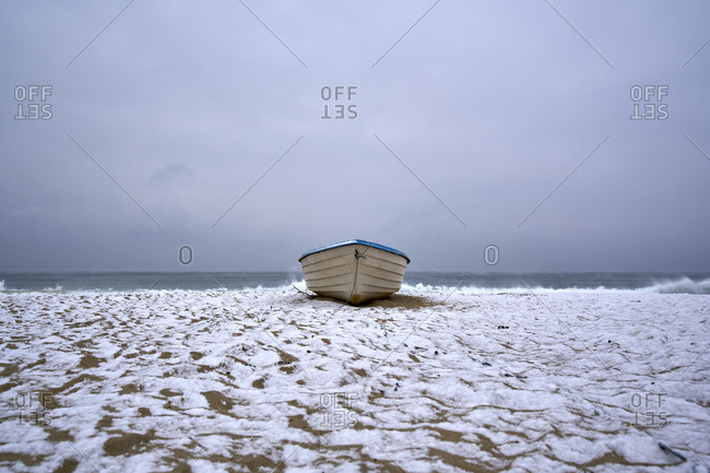 A boat beached on a beach covered by snow on the coast of Kamchiya reserve near Varna, Bulgaria