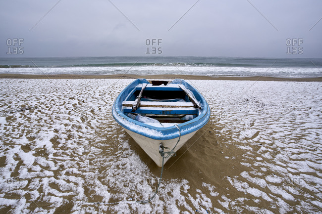 A blue and white boat beached on a beach covered by snow on the coast of Kamchiya reserve near Varna, Bulgaria