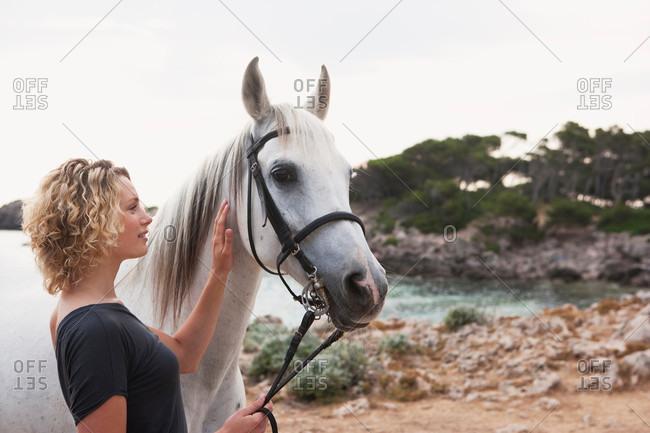 Woman petting a white horse