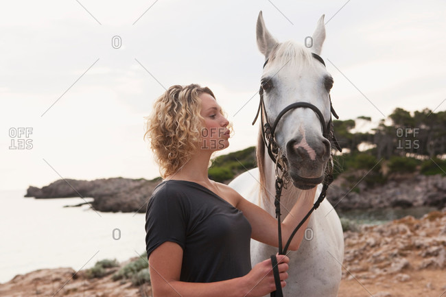Woman affectionately petting a white horse
