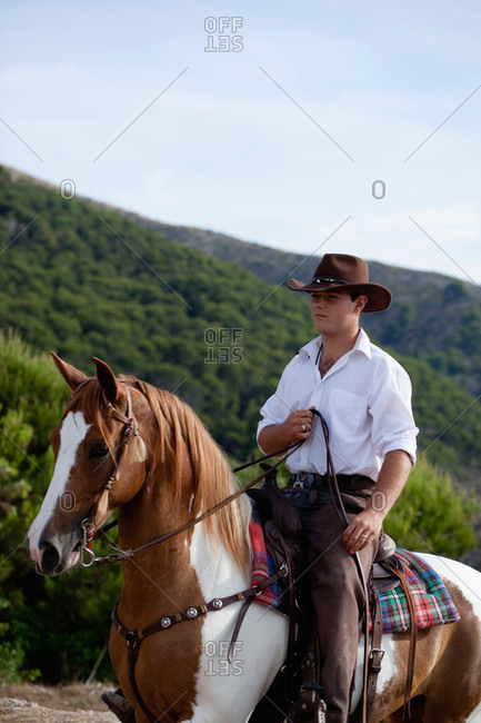 Young man wearing a cowboy hat riding a horse