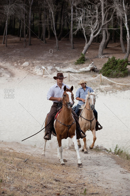 Men in cowboy hats riding horses together