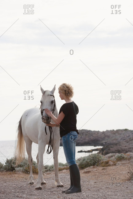 Woman and white horse by the coast