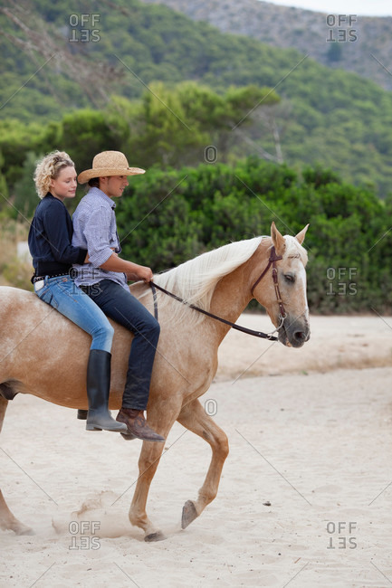 Young couple riding horse together