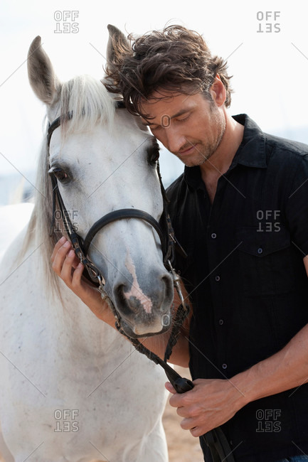 Man holding white horse's reins