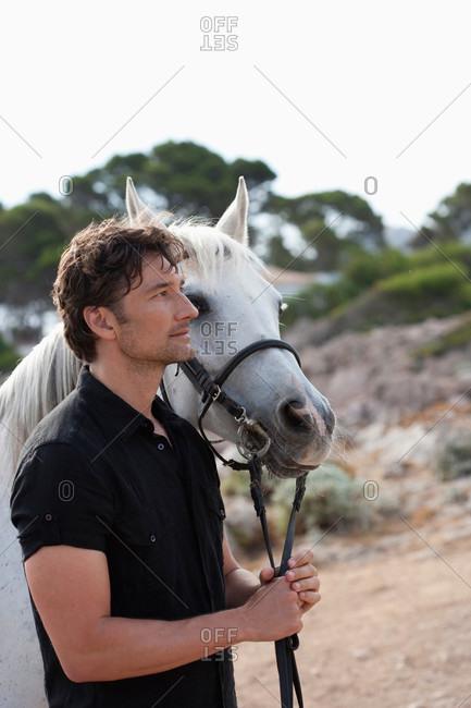 Man and horse walking along coast