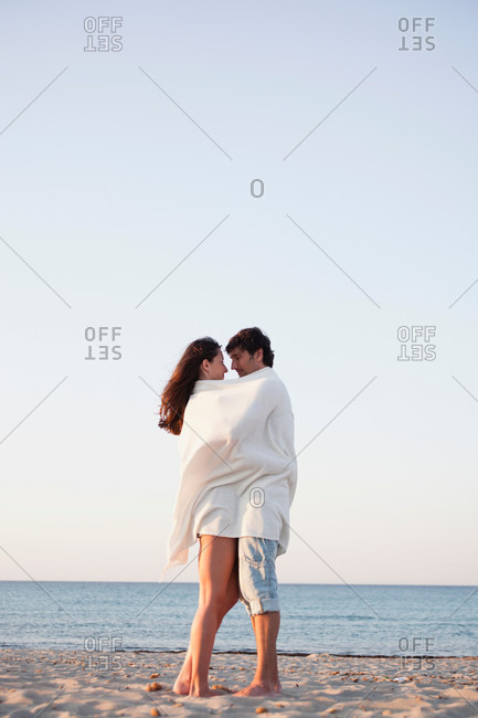 Couple cuddled up in beach towel