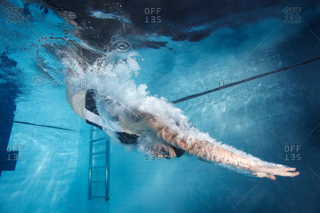Swimmer diving into a pool