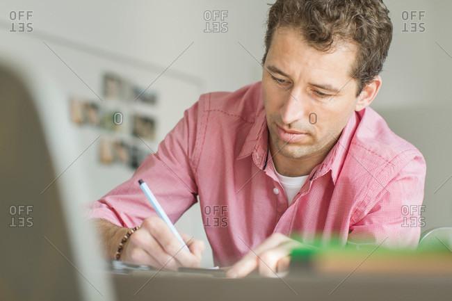 Man writing at a desk