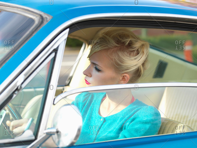 Woman sitting in vintage car