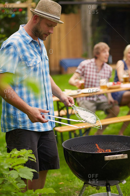 Man grilling fish on barbecue outdoors