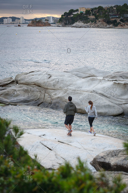 Couple walking on boulders by water