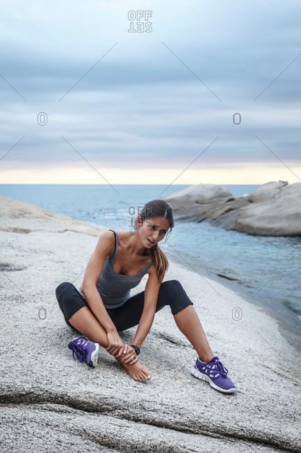 Woman massaging her ankle on boulder