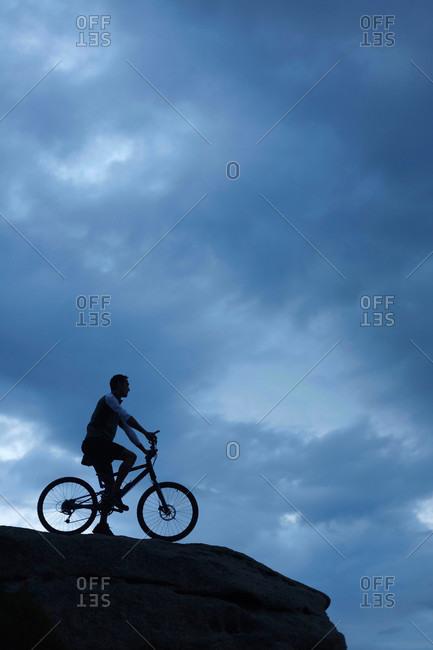 Man sitting on bicycle on boulder