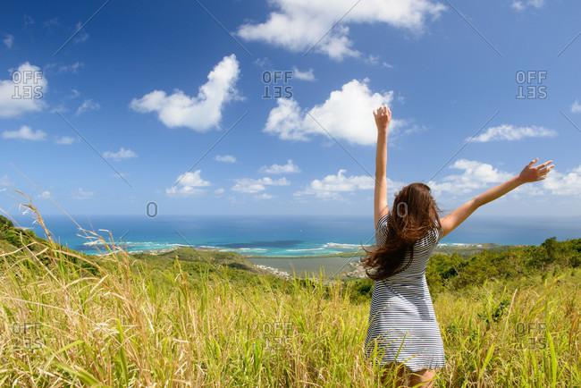 Woman walking in field of tall grass