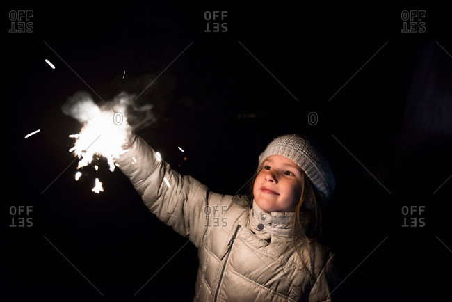 Girl playing with sparklers at night