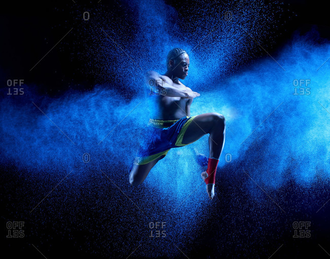 Young male boxer mid air with blue powder explosion