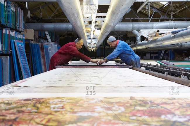 Two men printing fabric in factory