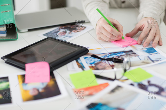 Man taking notes on desk with digital tablet and photographs